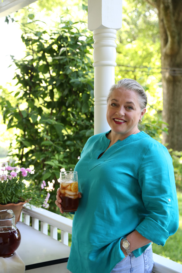 Virginia Willis relaxing on porch with glass of iced tea