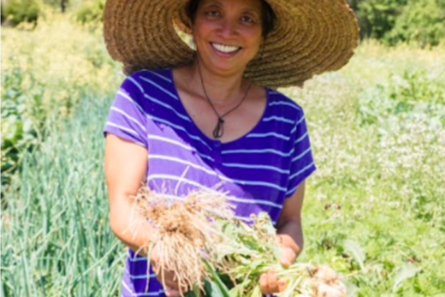 Jody of Jody's Farms holding a bushel of onions