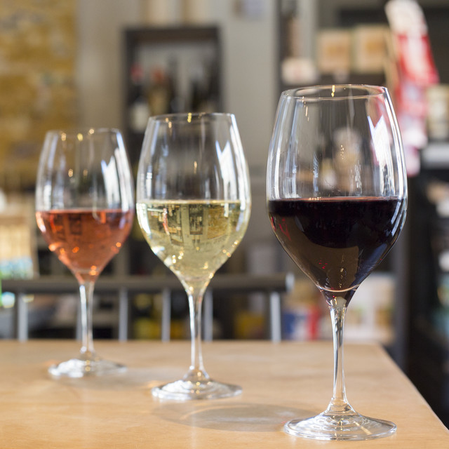Wine glasses of rose, white wine, and red wine in a wine shop.