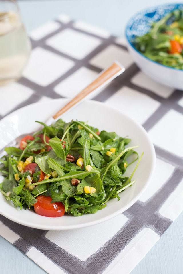 Arugula Salad with Corn, Tomatoes, and Pecans in a white bowl with a fork on a linen